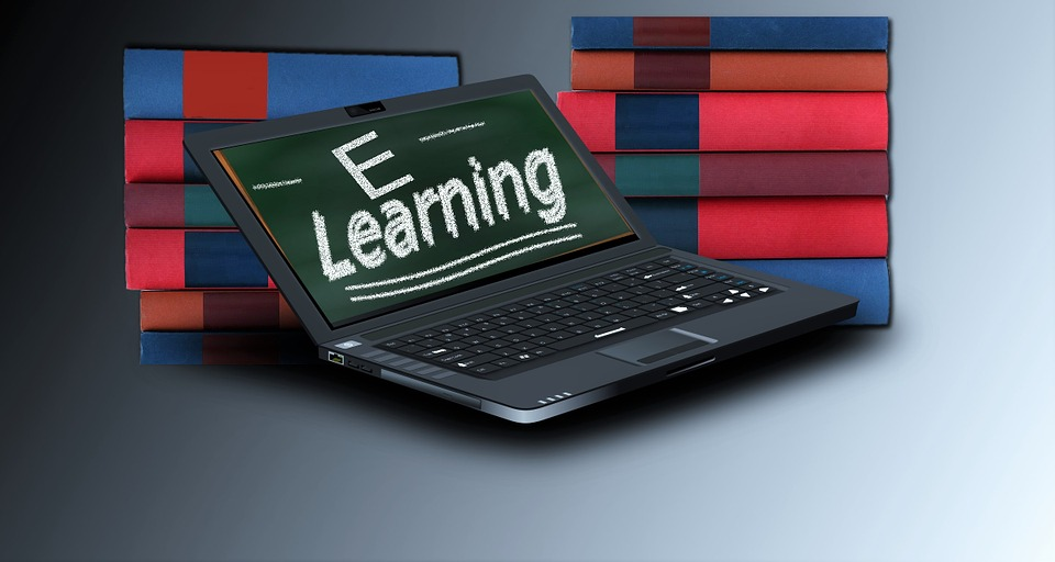 Laptop with e-learning on the screen against two piles of books