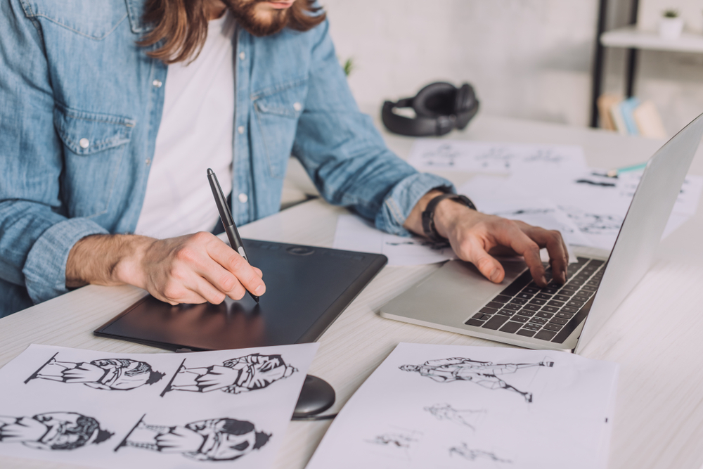 Cropped View Of An Animator Using Gadgets Near Sketches
